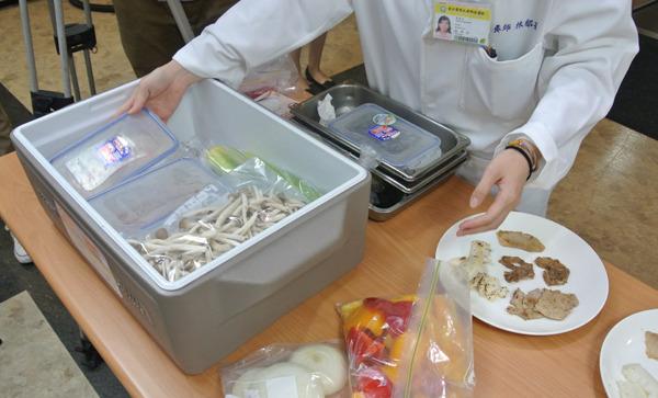 營養室膳食供應組組長林郁茹示範了食品保存方法,「先在保溫箱最底層舖上冰塊,再放上肉盒,最上層放入蔬菜水果盒即可。」(photo by 許瑋哲/台灣醒報)