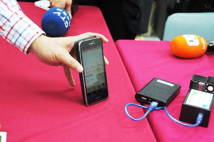 由檢測長、清大化學系教授凌永健推出簡便空氣品質監測器(右),民眾可以透過智慧型手機藍芽連接,之後就能將監測數據傳到網站上。(photo by 黃譯萱/台灣醒報)