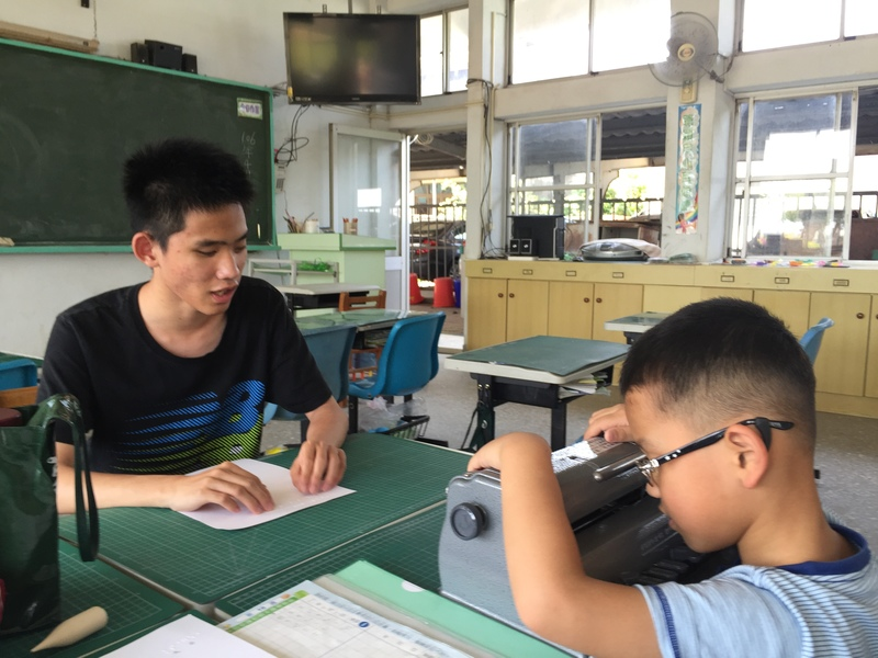 嘉義市嘉義高中二年級陳柏翰教導盲生使用點字機。(photo by保德信青少年基金會)
